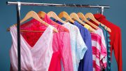 colorful womens clothes on wood hangers on rack on blue backgrou