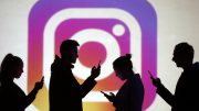 Image: Silhouettes of mobile users are seen next to a screen projection of Instagram logo in this picture illustration